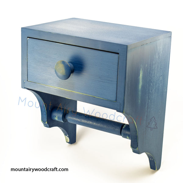 A wooden toilet tissue holder with convenient storage drawer. The storage drawer can be used to keep personal hygiene products discreetly close at hand.