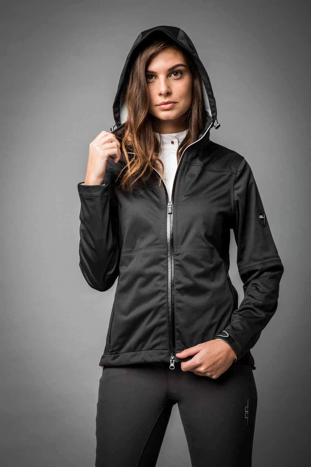 Stay dry and fly with the Horseware Ireland Acqua Ladies Waterproof Jacket!  Waterproof & breathable 3000/3000  / Fully Taped seamed  / 4 ways stretch  Feminine style lines  with a hidden hood with peak visor  2 front pockets with zips  / Two-way central zip closure  Soft Tabs for adjustable cuffs  100% Polyester 3000/3000 knit fabric  Machine washable
