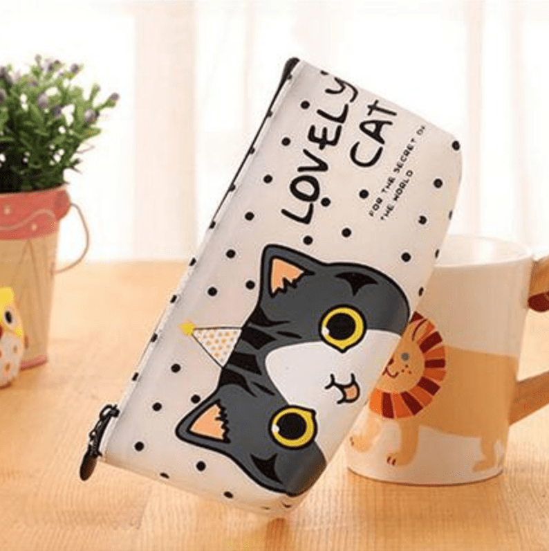 cat themed pencil case next to cup