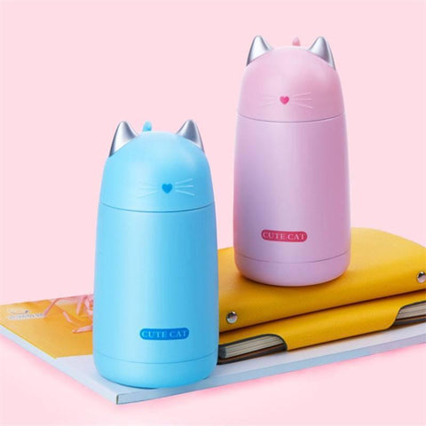 pink and blue cat thermos on books and folder