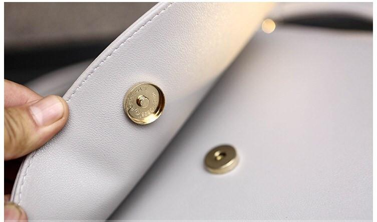 Side View of Cat Moon Leather Handbag Showing button lock - White on Desk