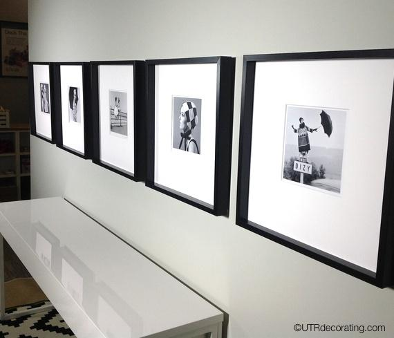 Five frames hung in a row above a table