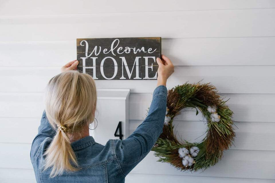 Blond woman hanging a welcome sign