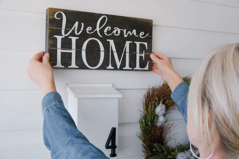 blonde woman hanging welcome sign