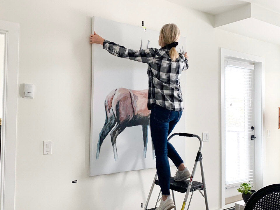 women hanging a large deer canvas on the wall