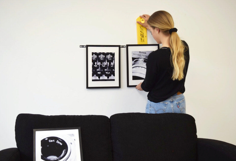 hanging three frames above a couch
