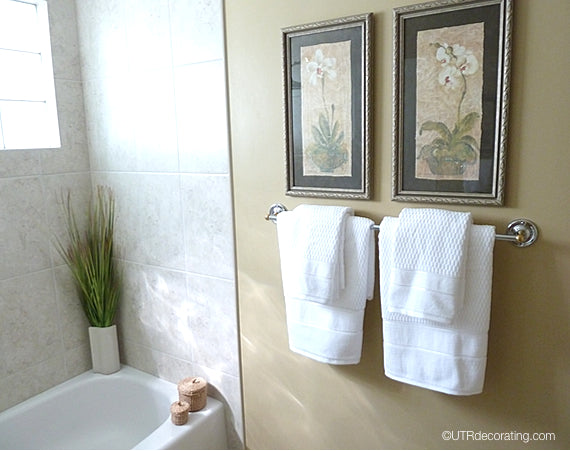 Create a focal point in your bathroom by hanging pictures above a towel rack