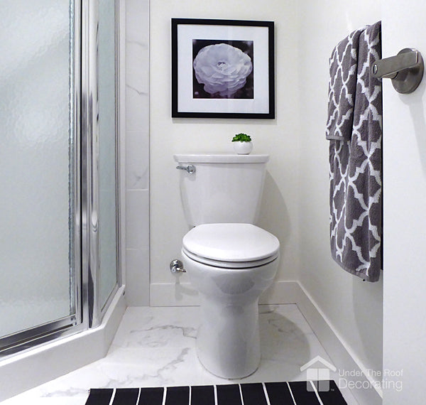 A black and white floral print shows how hanging art in a bathroom is a great way to create a focal point