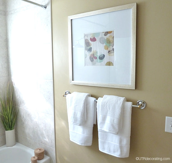 Create a focal point the bathroom by hanging a picture above the towel rack