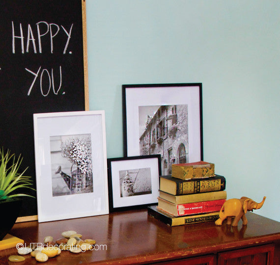 black and white frames and vintage books on a dark wood table against a teal wall