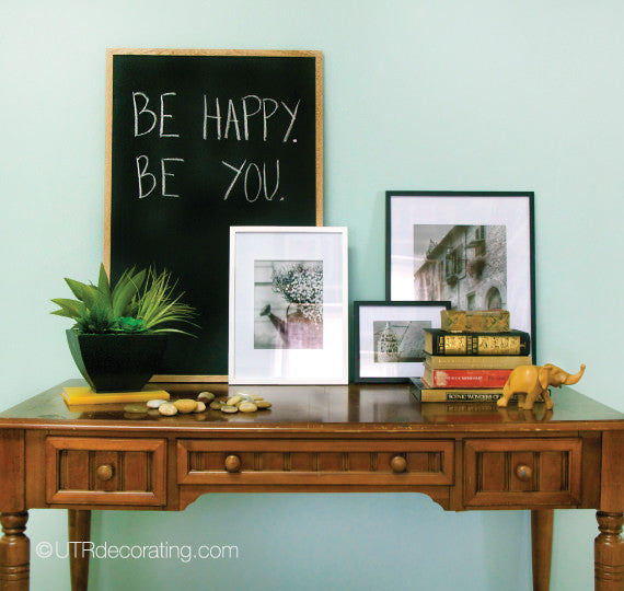 vintage table with framed photos and accessories against a light teal wall