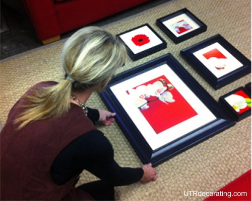 laying frames on the floor before hanging a group of pictures