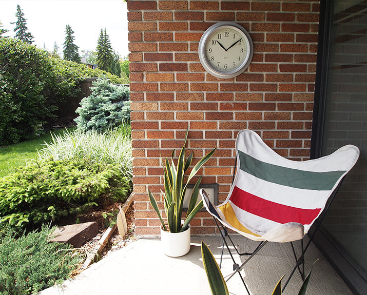 clock hanging on outdoor brick with white chair and plant