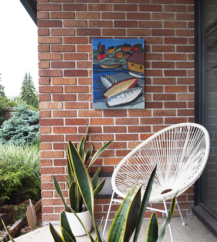 painting hanging on brick with white basket chair and plants
