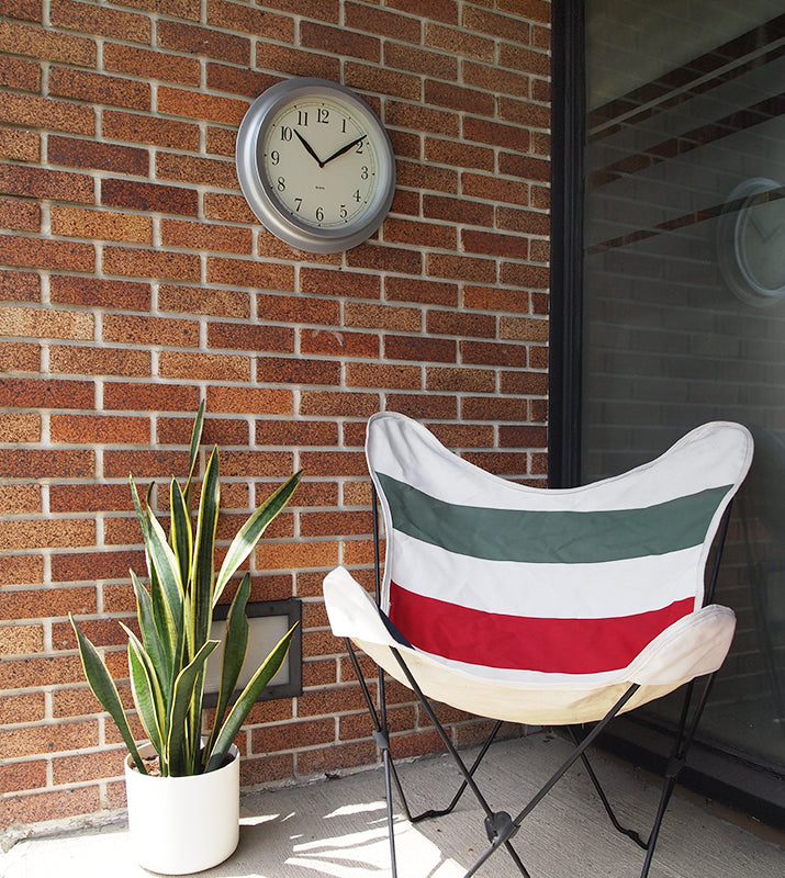 Clock hanging on brick wall with a chair and plant