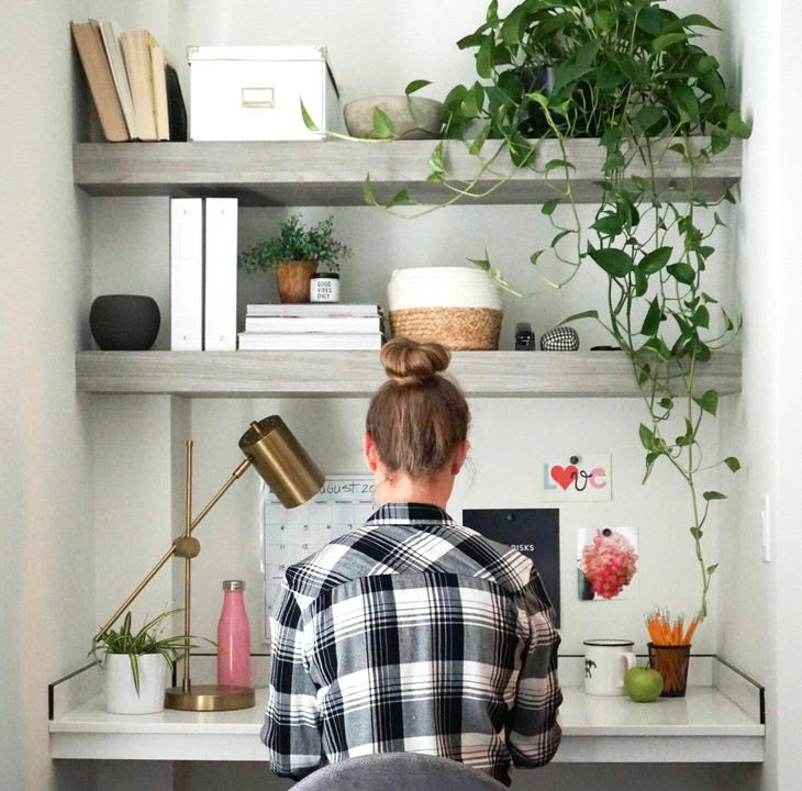 girl sitting at a desk with shelving above it