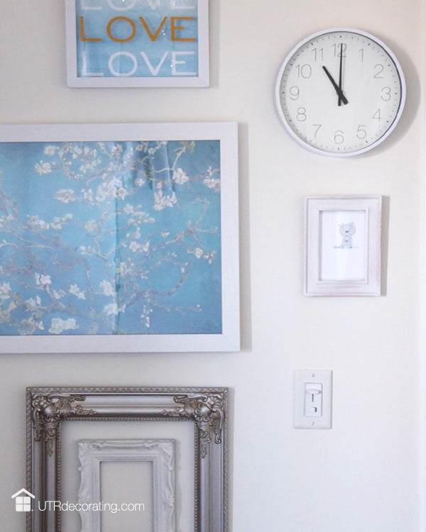 frames and a clock create a gallery for a small wall
