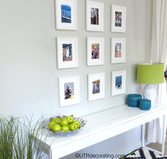 Hallway table placed under gallery wall made with summer vacation photos
