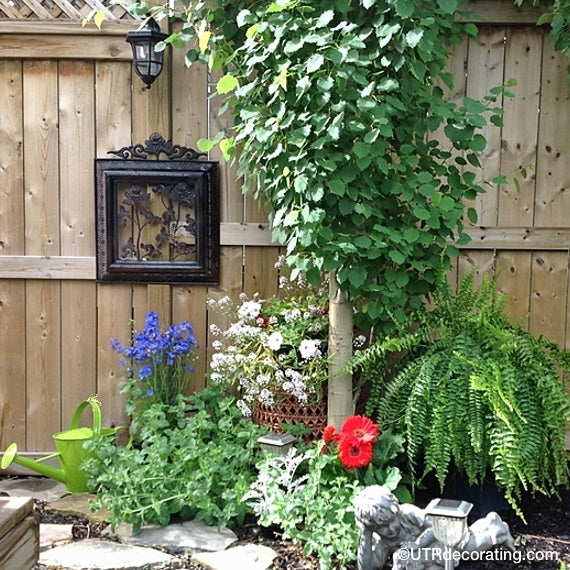 vintage outdoor decor idea: metal ornament hanging on a fence