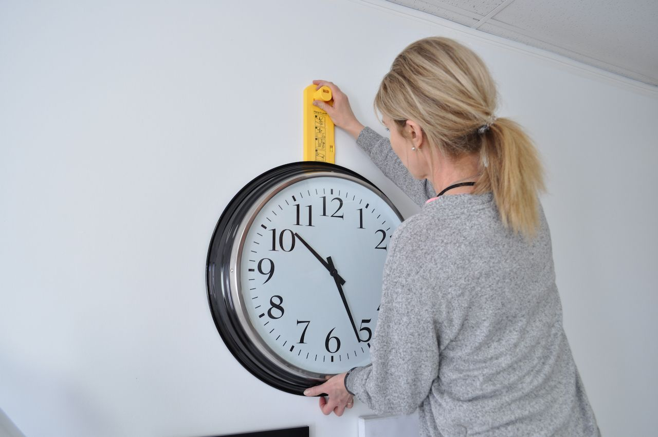 woman hanging clock with Hang&Level