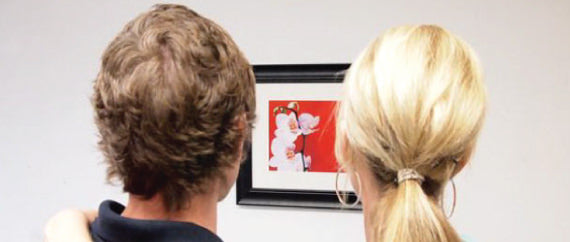 couple looking at a large picture with d rings on the wall