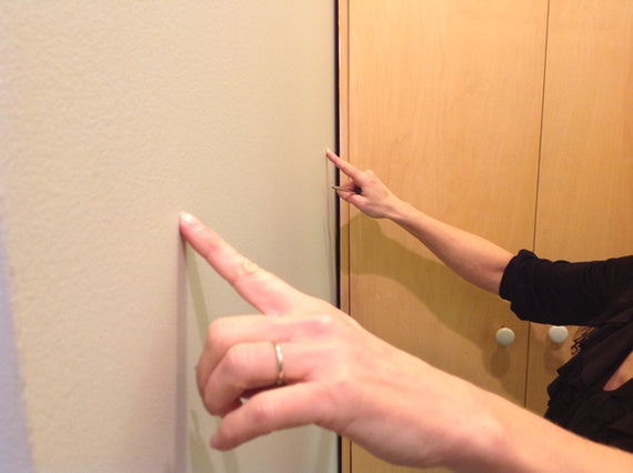 pointing out the spots for the screws to hang our full length mirror