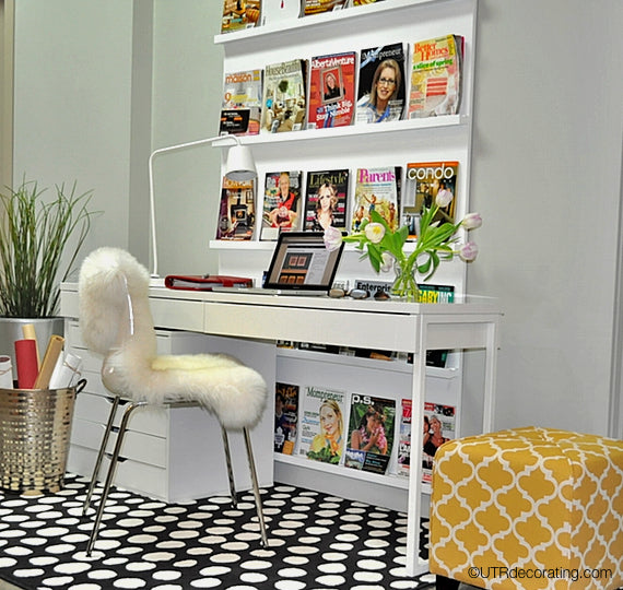 IKEA skinny white desk placed in front of magazine rack creates an inviting reception area