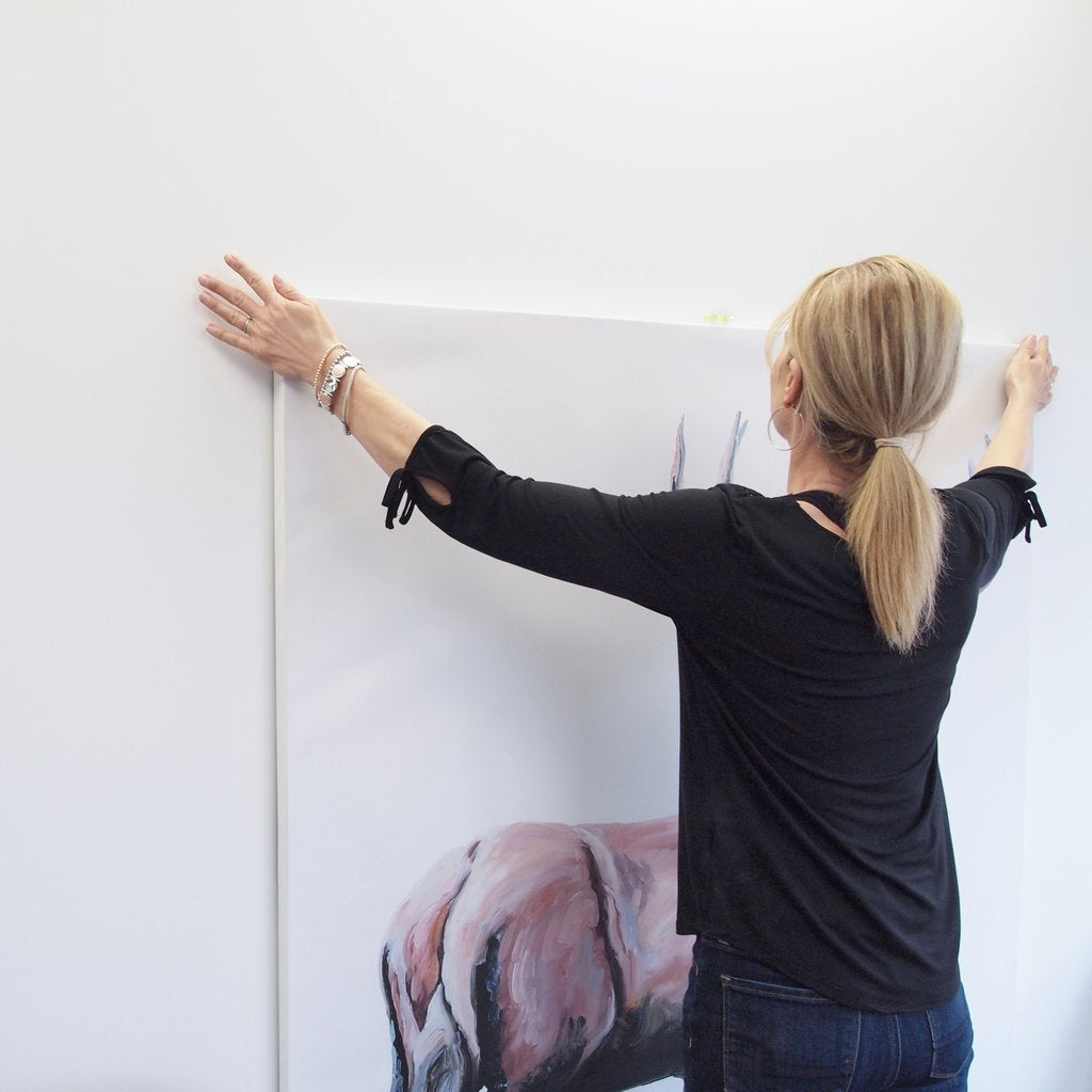 woman hanging large canvas