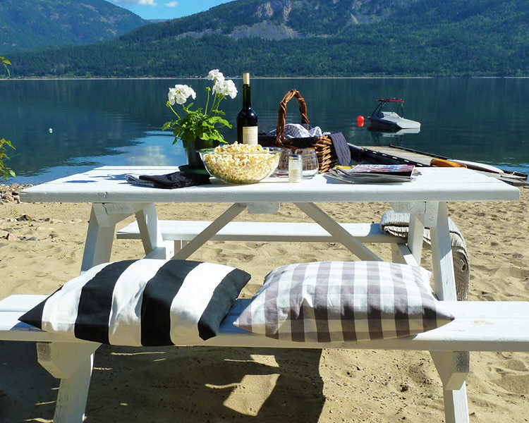 Chic white painted picnic table on beach ready to dine in class
