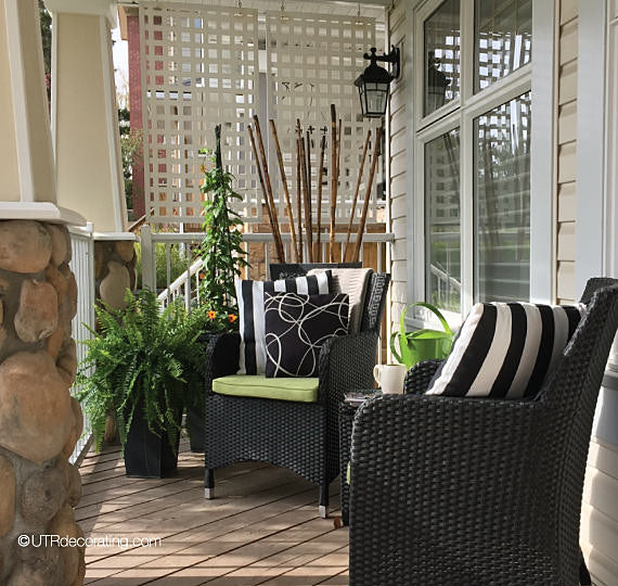 Black & white cushions provide a chic look when decorating a front porch for summer: