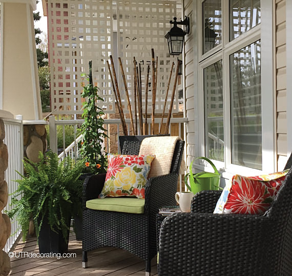 Decorating the front porch for summer with wicker furniture, plants and floral cushions