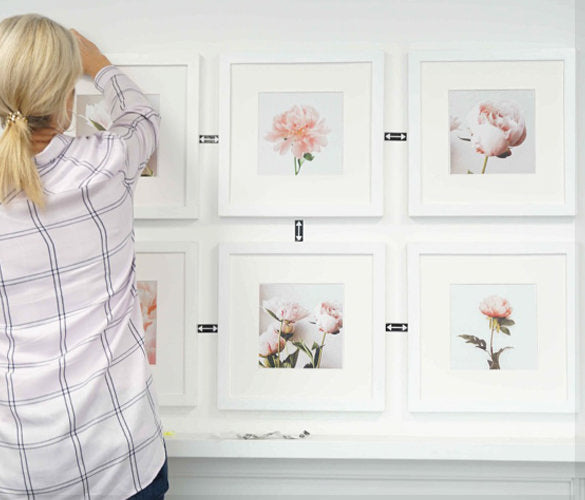 Women applying SpacingStrips to her gallery wall to achieve perfect spacing