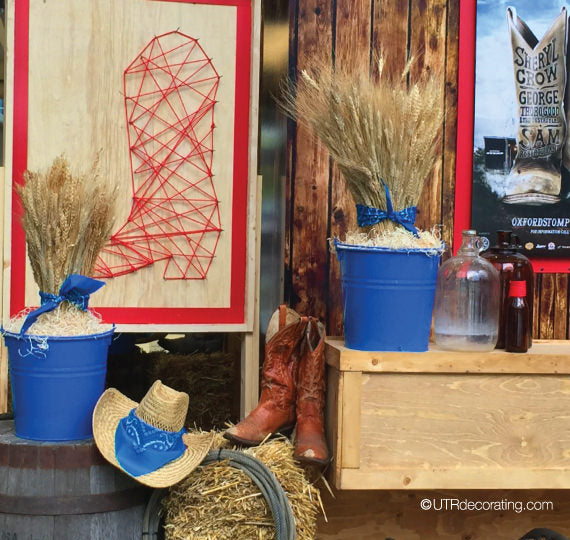 western decorating with straw planters, cowboy boots and a cowboy hat