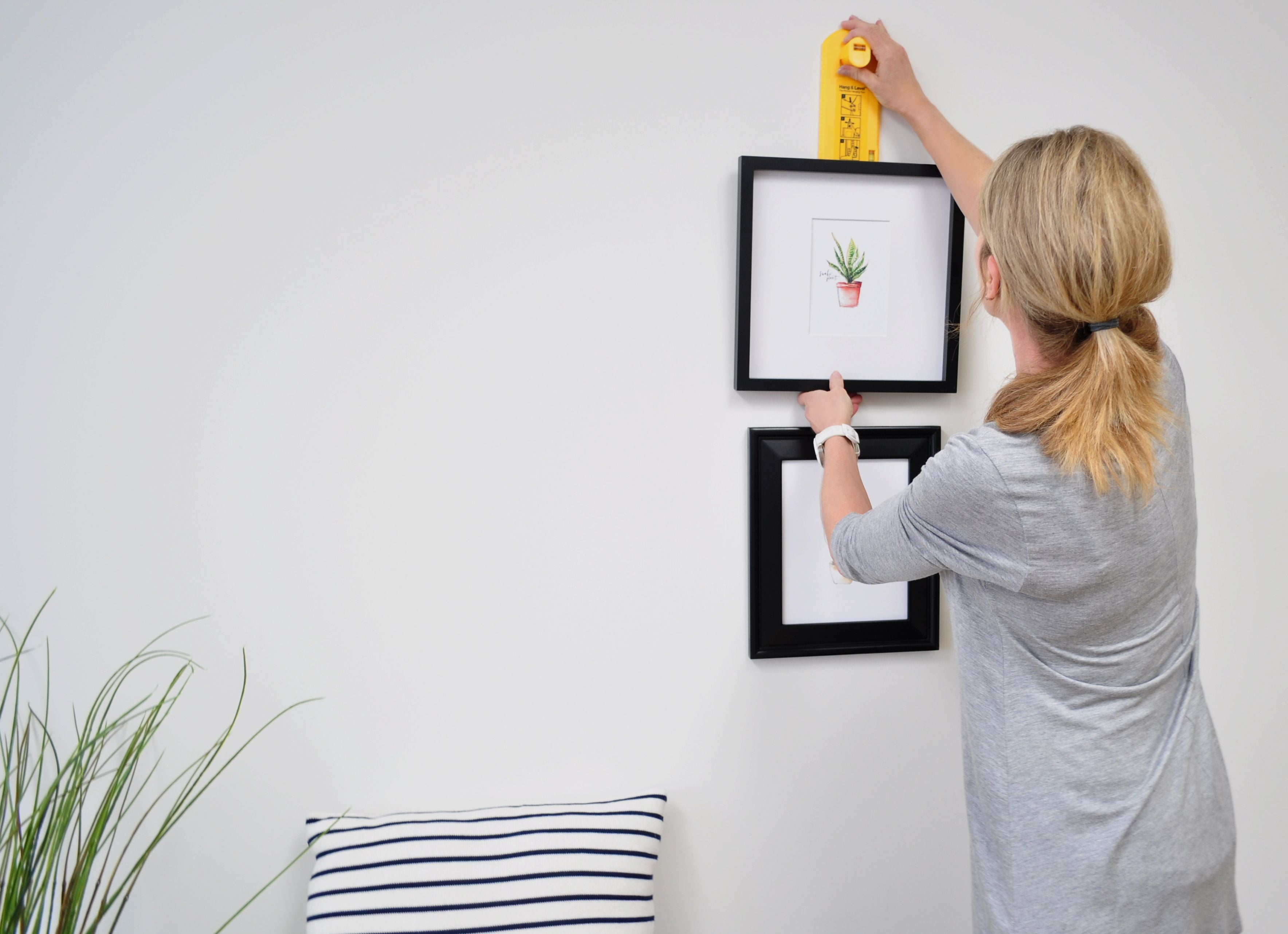 woman hanging picture with Hang & Level