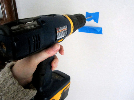 drilling through painters tape on a plaster wall