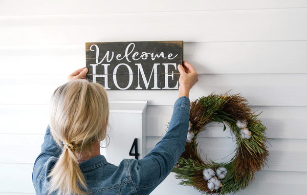 "Blonde woman hanging ""welcome Home"" sign above mailbox"