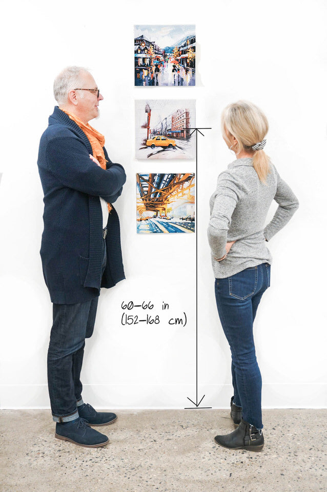 man and women standing next to 3 canvases hung vertically with the center of the arrangement at eye level