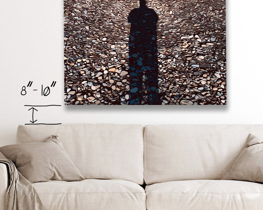 canvas hung 8-10 inches above a beige couch