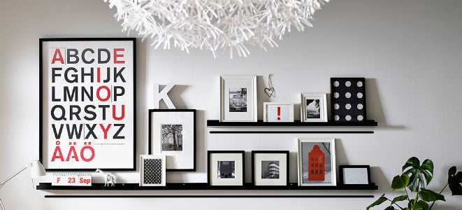 2 floating shelves holding a variety of black and white frames