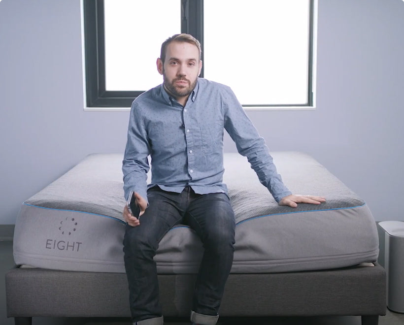man sitting on edge of Eight Sleep Pod Mattress