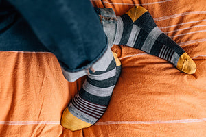 Feet wearing darn tough strut men's lifestyle socks with roosters on them, a fun everyday casual sock or casual dress sock for men
