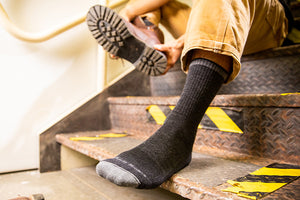 Man pulling on darn tough men's work socks for steel toe boots
