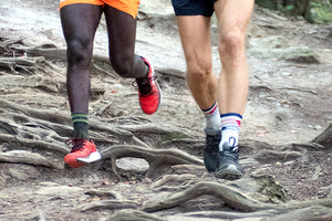 A trail runner stopped on a rock wearing running shoes and our new darn tough men's running socks with cushion