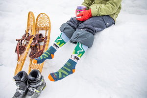 An adorable girl wearing our kids ski and snowboard socks on her hands to hold a hot cocoa mug. These are great ski gifts for kids - just saying