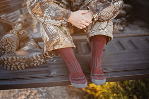 A lady hunter seated at camp wearing camo and darn tough women's hunting socks
