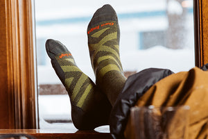 Snow boarder putting on boots wearing men's ski and snowboard socks