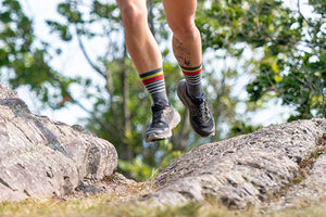 A woman stopped while trail running wearing running shoes and our new darn tough women's running socks