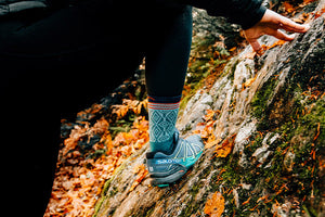 Woman wearing darn tough women's hiking socks with her sandals while chilling on a rock by a stream on trail