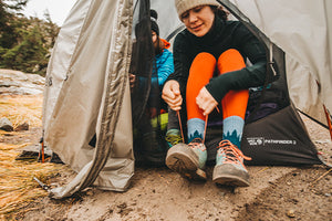 A hiker sitting on a rock wearing darn tough women's socks, the best socks for women for every activity