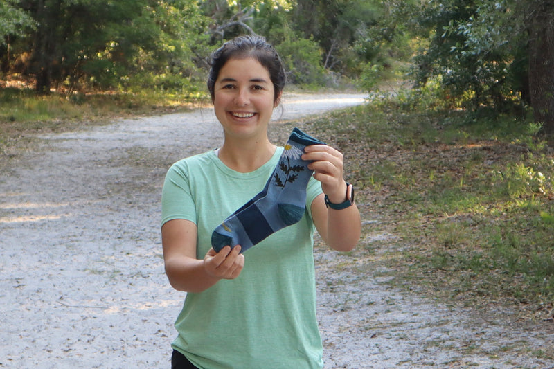 Thru hiker Emily holding her favorite hiking socks, the Queen Bee